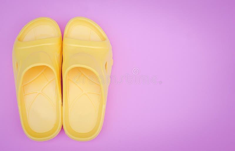 Härlig gul sandal på rosa pastellfärgad bakgrund med kopieringsutrymme royaltyfri foto