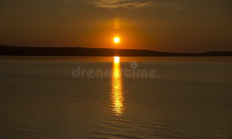 Härlig guld- orange solnedgång över sjön Solen ställer in att vända himlen gula, orange & röda signaler & reflekterar i sjön arkivfoton