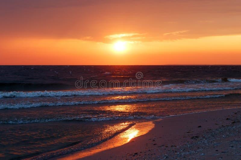 Härlig guld- solnedgång i havet med genomdränkt himmel och moln Reflexion i vattnet Stenig kust- linje Fridsamt fridfullt LAN royaltyfri fotografi