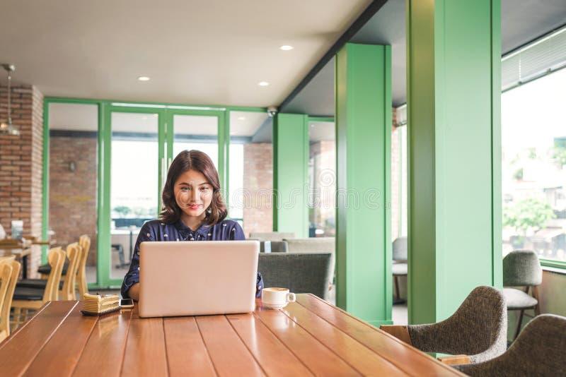 Härlig gullig asiatisk ung affärskvinna i kafét, genom att använda lapt royaltyfria bilder
