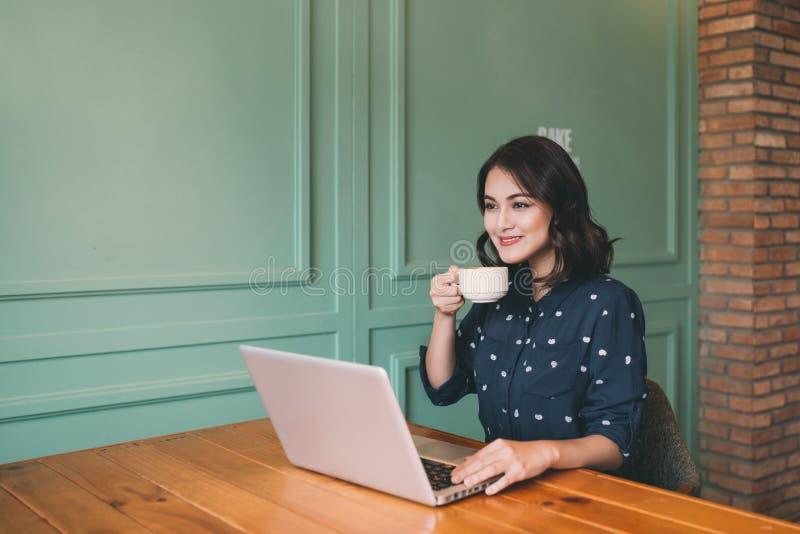 Härlig gullig asiatisk ung affärskvinna i kafét, genom att använda lapt fotografering för bildbyråer