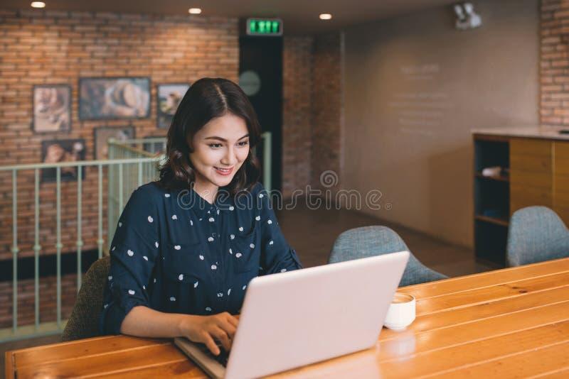 Härlig gullig asiatisk ung affärskvinna i kafét, genom att använda lapt royaltyfria foton