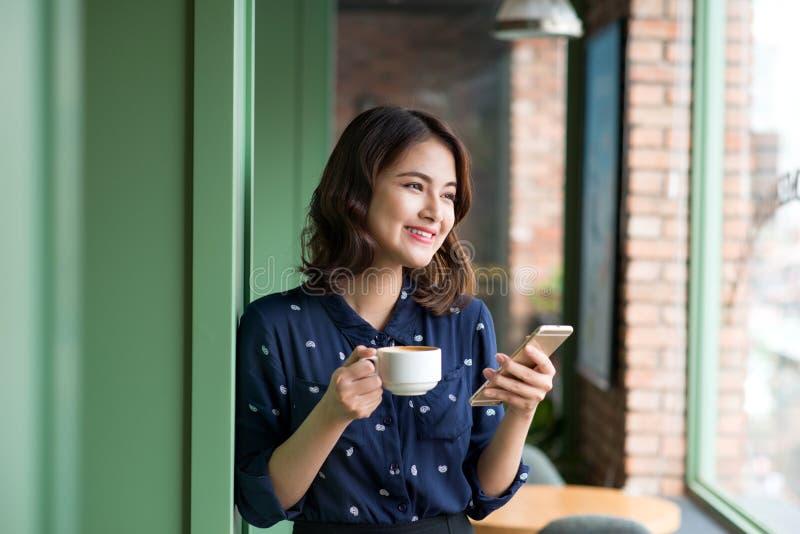 Härlig gullig asiatisk ung affärskvinna i kafét, genom att använda mobi fotografering för bildbyråer
