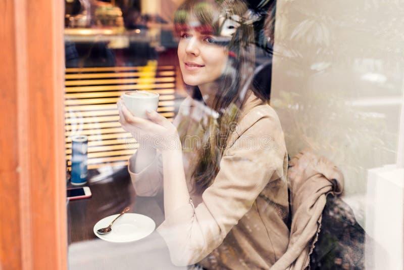 Härlig gullig flicka i kafét nära fönstret med att le för kaffe fotografering för bildbyråer