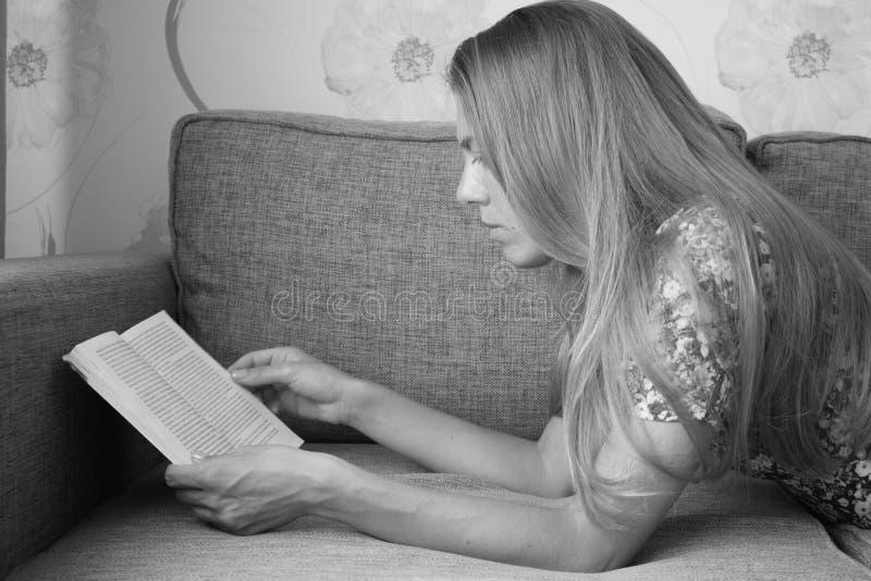 Härlig gullig flicka som ligger på soffan och läsningen en bok arkivfoton