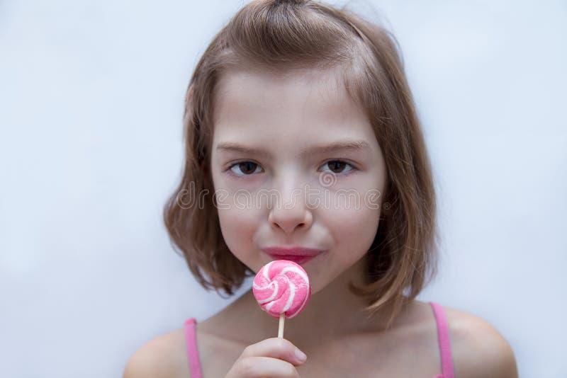 Härlig gullig liten flicka som äter klubban arkivbild