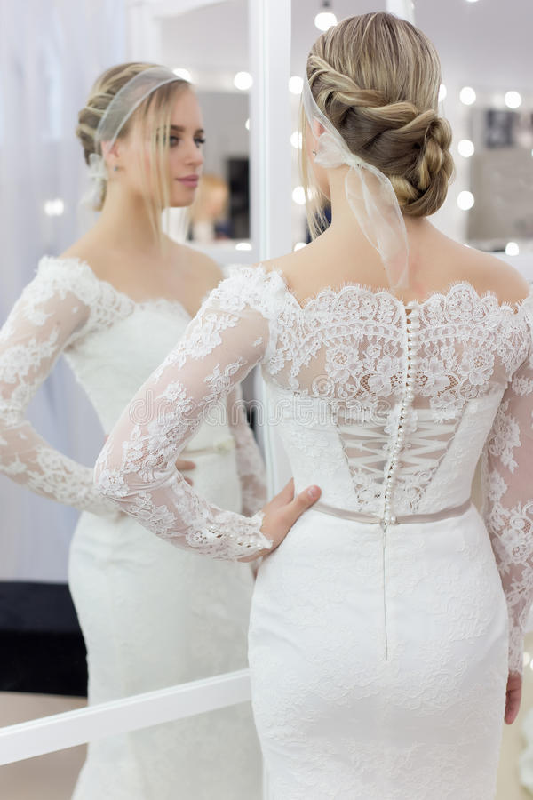 Härlig gullig mjuk ung flickabrud i bröllopsklänning i speglar med aftonhår och försiktigt ljust smink arkivbild
