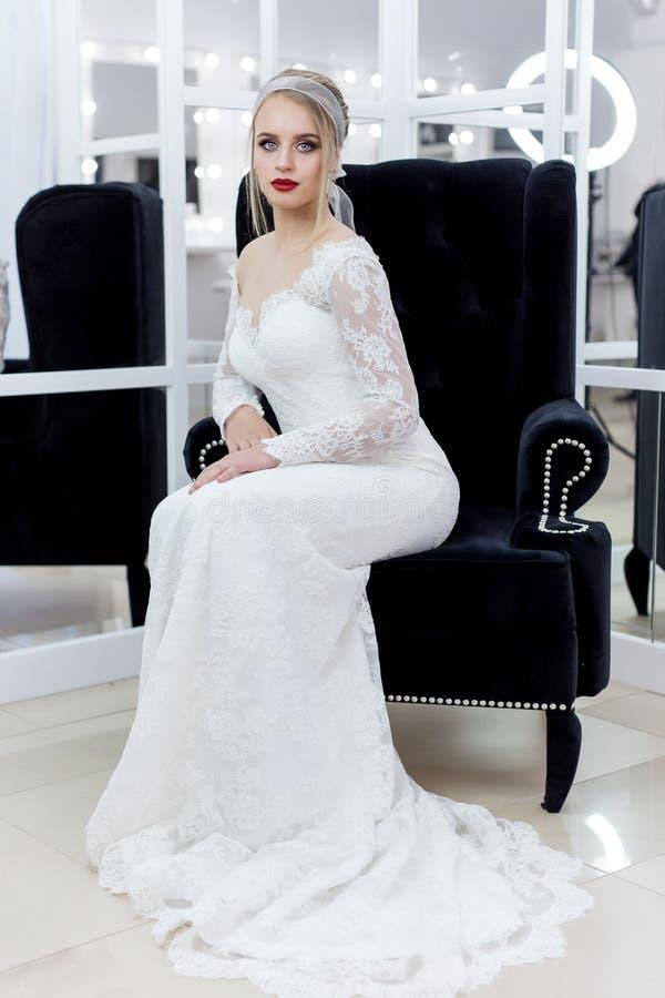 Härlig gullig mjuk ung flickabrud i bröllopsklänning i speglar med aftonhår och försiktigt ljust smink royaltyfria foton