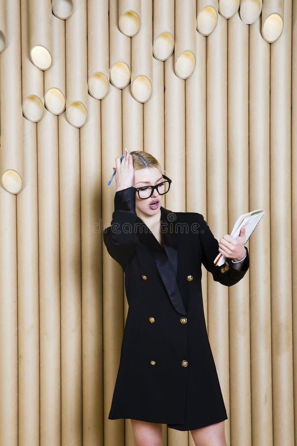 Härlig häpen blond affärskvinna i svart klänning och exponeringsglas arkivfoton