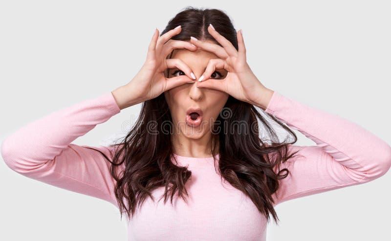 Härlig häpen kvinna som bär den rosa tillfälliga dräkten som rymmer hennes händer på hennes ögon som, om se till och med kikare e arkivbilder