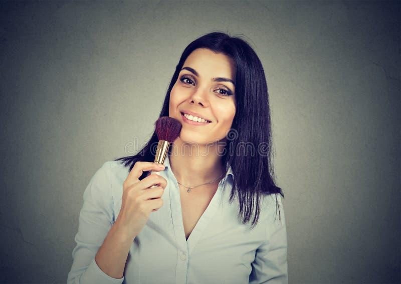 Härlig hållande makeupborste för ung kvinna i hand royaltyfri fotografi