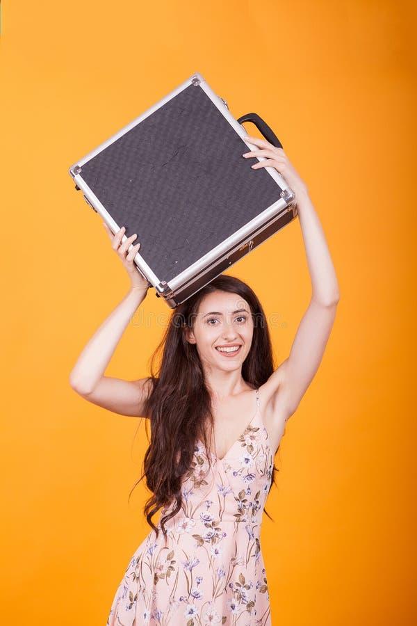 Härlig hållande portfölj för ung kvinna i studio över gul bakgrund arkivbilder