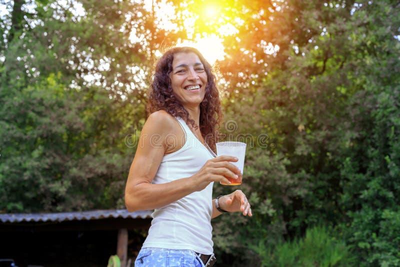 Härlig hållande sodavatten för ung kvinna och le på sommar royaltyfri bild