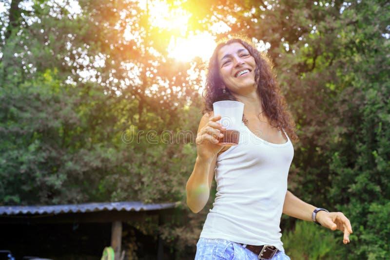 Härlig hållande sodavatten för ung kvinna och le på sommar royaltyfria foton