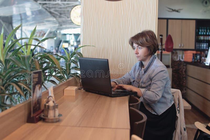 Härlig hög affärskvinna som sitter på kafét som har telephonic konversation med klienten Mogen kvinnlig affär royaltyfri bild