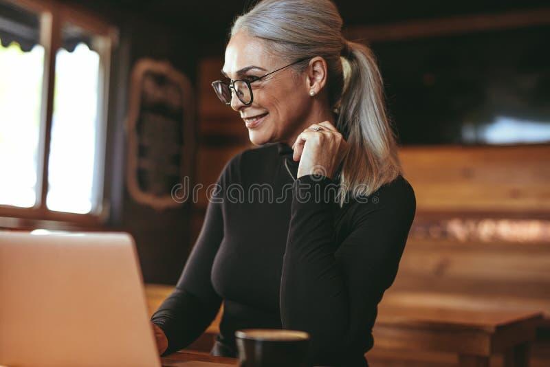 Härlig hög kvinna på kafét genom att använda bärbar datordatoren royaltyfri foto