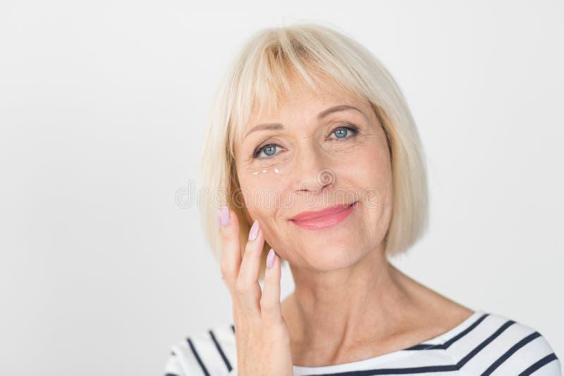 Härlig hög kvinna som applicerar anti--skrynkla framsidakräm arkivbilder