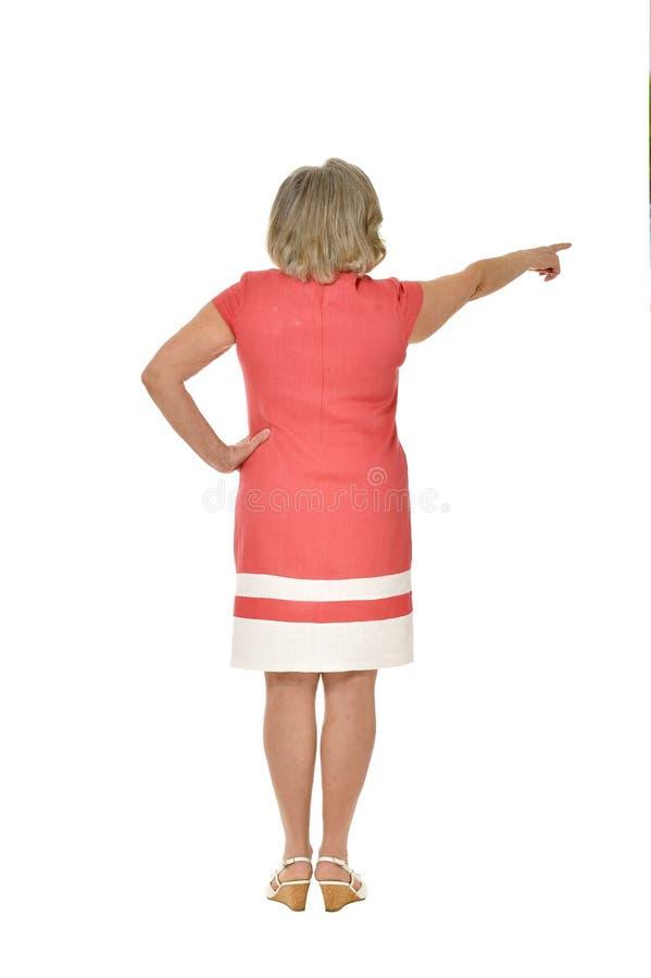 Härlig hög kvinna som pekar på vit bakgrund royaltyfria foton