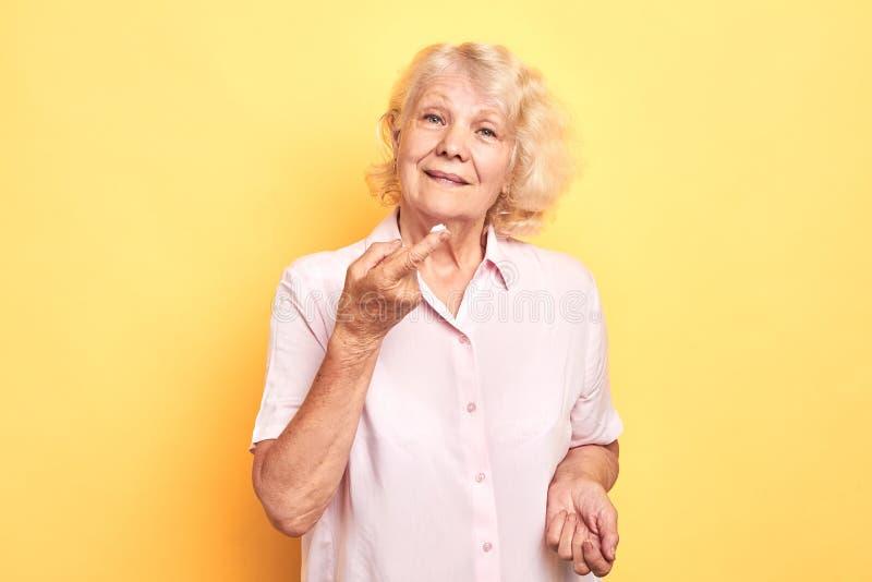 Härlig hög kvinna som sätter på krämen med fingret på hennes framsida royaltyfria bilder
