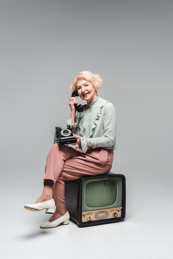 härlig hög kvinna som talar vid den roterande telefonen, medan sitta på tappningtv arkivbild