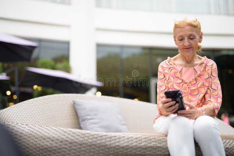 Härlig hög turist- kvinna med blont hår som kopplar av runt om t royaltyfria bilder
