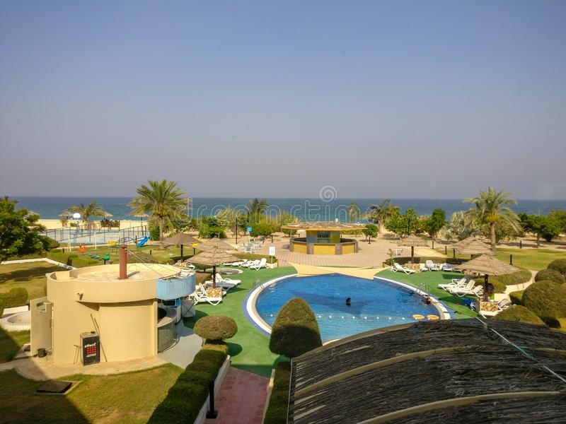 Härlig högklassig tropisk sommarsemesterort i Oman med en simbassäng och en strand arkivfoto