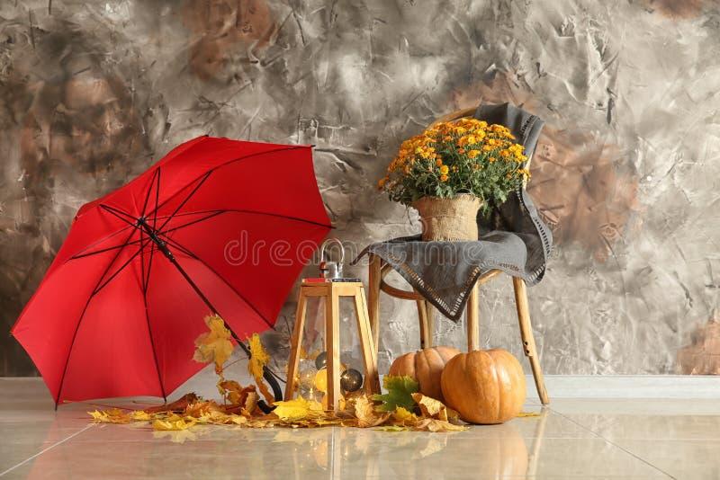 Härlig höstsammansättning med pumpor, sidor och paraplyet nära färgväggen arkivbild