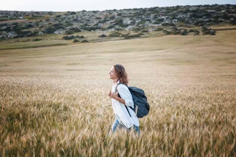 Härlig handelsresande för ung kvinna som går på ett vetefält royaltyfri foto