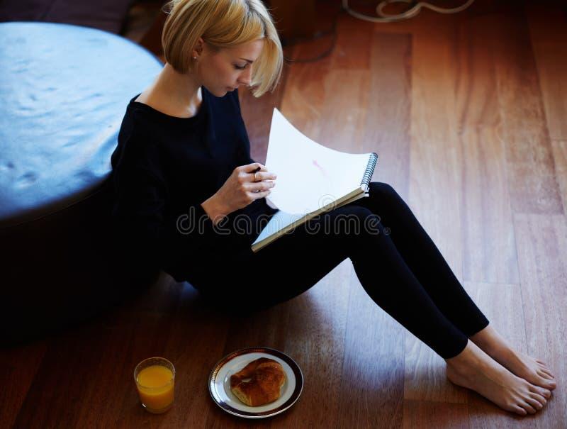 Härlig handstil för ung kvinna något i anteckningsboken, medan sitta på golvet på vardagsrum arkivfoton