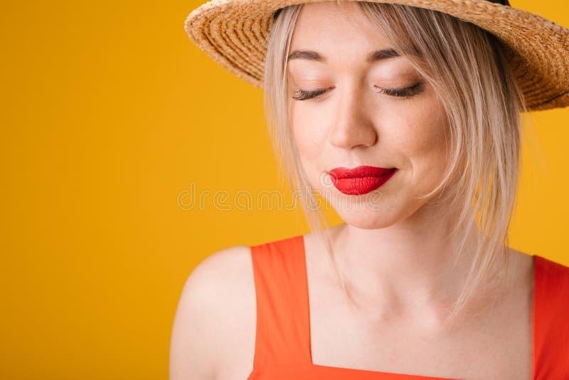 härlig hattsugrörkvinna stängda ögon Gul sommarlynnebakgrund eftertänksam drömlik framsida royaltyfri fotografi
