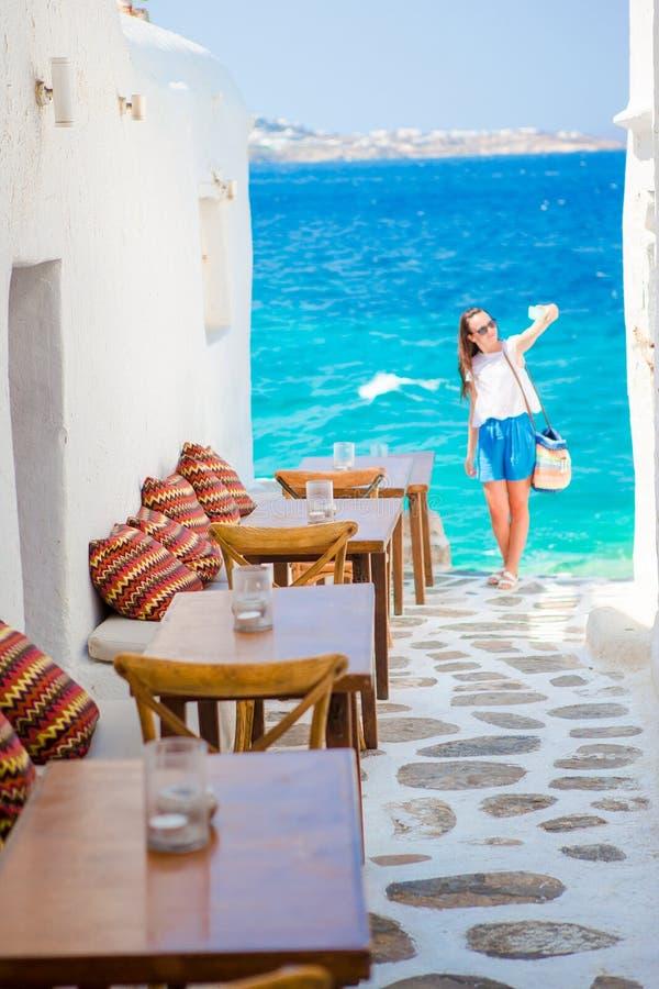 Härlig havssikt i det utomhus- kafét Mykonos på Cyclades öar Ung kvinna som tar selfie med denna fantastiska sikt arkivfoto