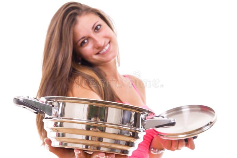 Härlig hemmafru för ung kvinna med en kökkastrullkruka royaltyfri fotografi