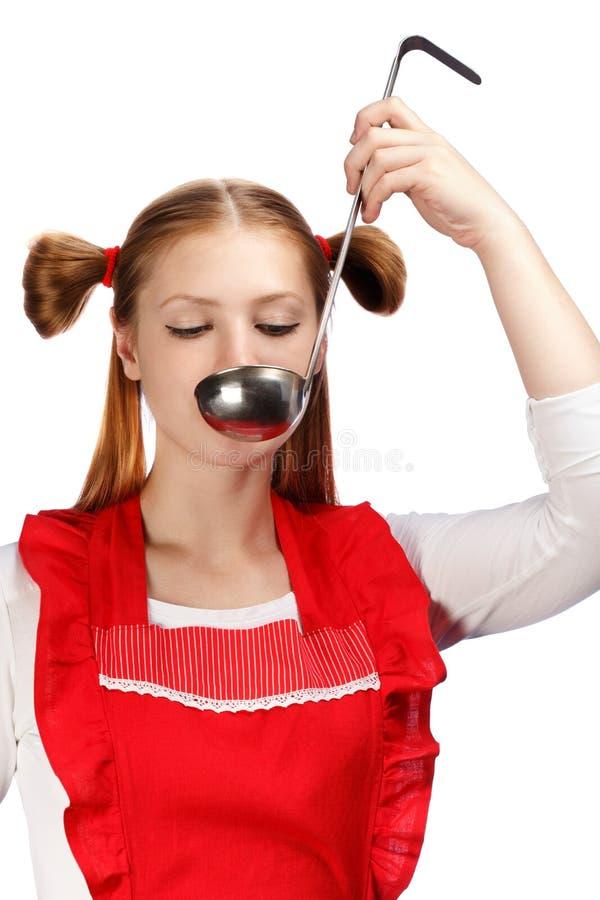 Härlig hemmafru i rött förkläde med roliga hästsvansar som smakar mig arkivbild