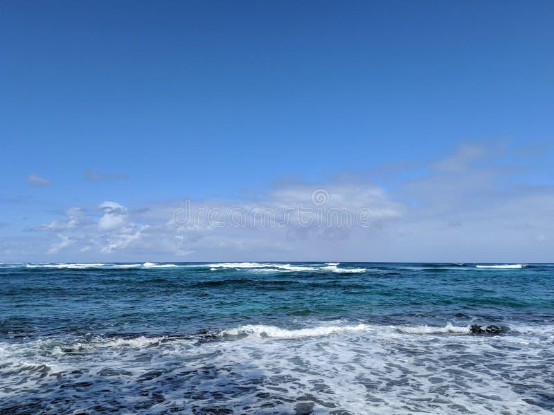 Härlig himmel över havet med vågor som rullar in mot kusten på den norr kusten arkivbild