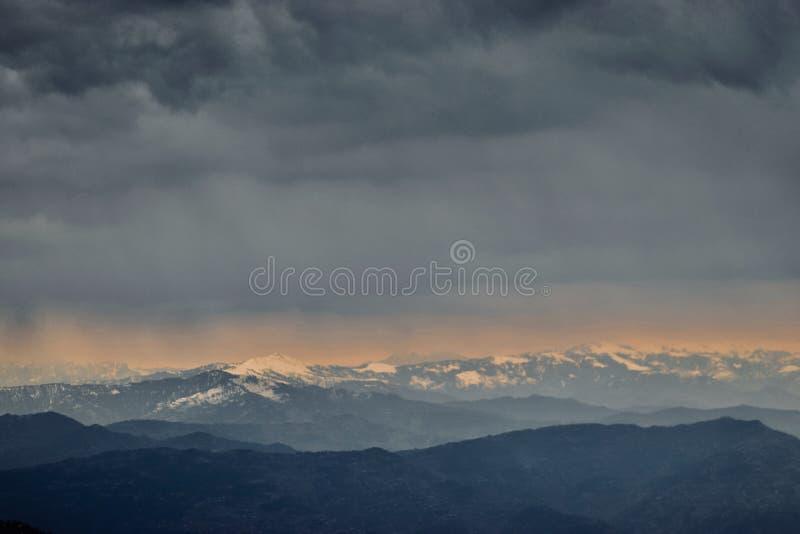 Härlig himmel med moln över snöig berg arkivbilder