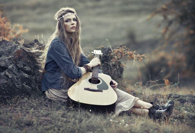 Härlig hippieflicka med gitarren royaltyfria foton