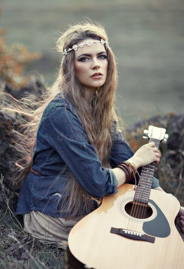 Härlig hippieflicka med gitarren royaltyfri foto