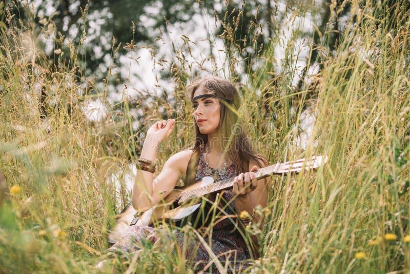Härlig hippieflicka med gitarren som sitter på skoggläntan royaltyfri fotografi