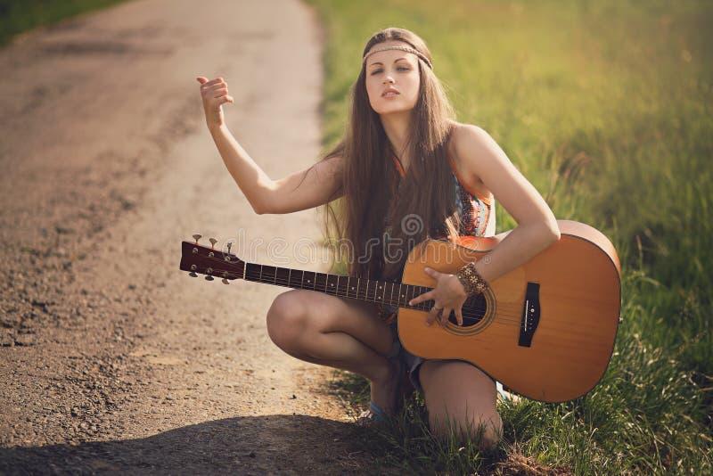 Härlig hippiehake-fotvandrare med gitarren royaltyfria bilder