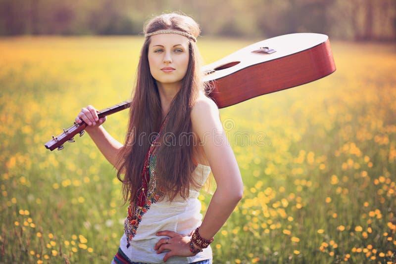 Härlig hippiekvinna med gitarren arkivfoto
