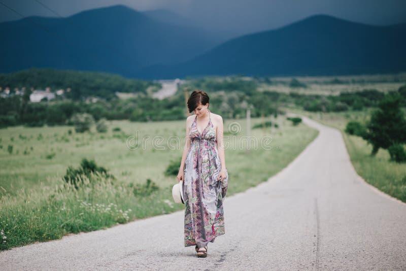 Härlig hippiekvinna som poserar på ett grönt fält med berg på bakgrunden royaltyfria bilder