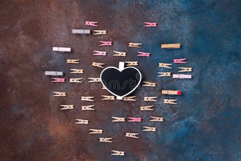 Härlig hjärta gjorde av klädnypor med ett kritabräde och utrymme för text på stenbakgrund - valentins dagbegrepp arkivfoto