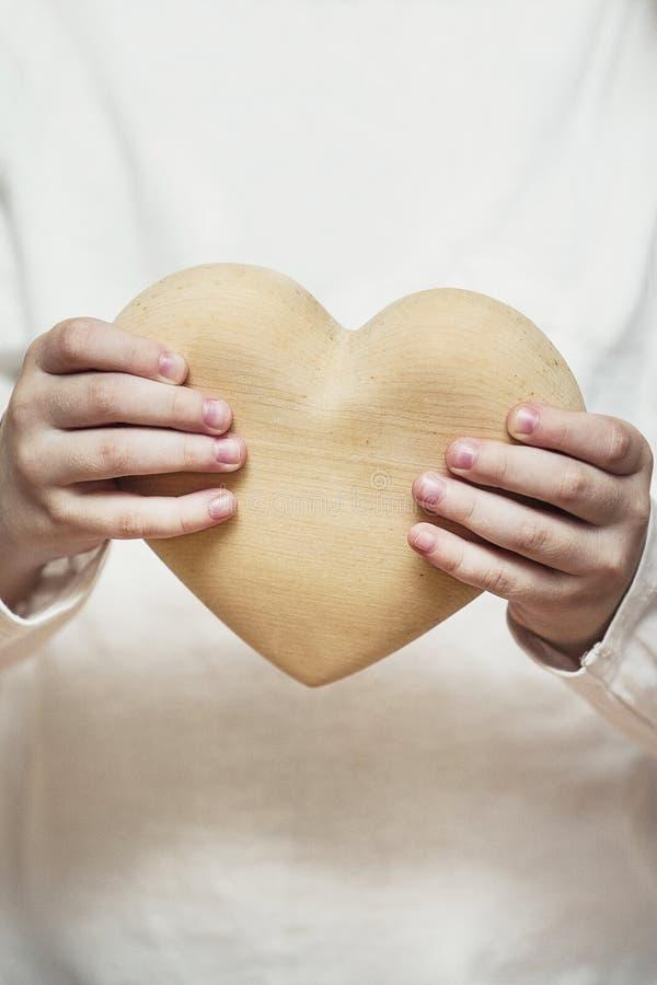 Härlig hjärta som göras av trä i barnhänder royaltyfria bilder