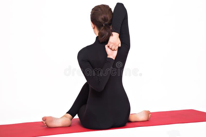 Härlig idrotts- flicka i den svarta dräkten som gör yoga gomukhasanaasanaen - posera kons huvud bakgrund isolerad white royaltyfri foto