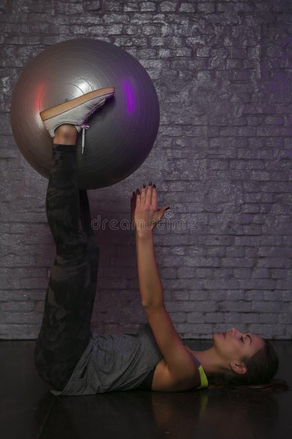 Härlig idrotts- flicka som öva med en boll på idrottshallen, nätt kontur royaltyfri foto