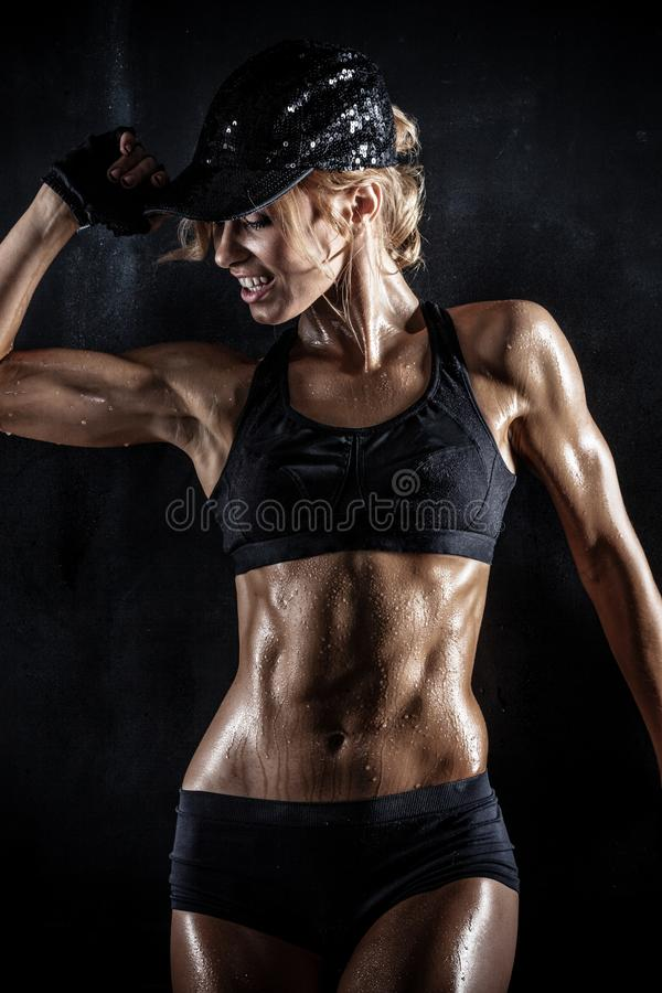 Härlig idrotts- kvinna i locket som poserar på mörker arkivbilder