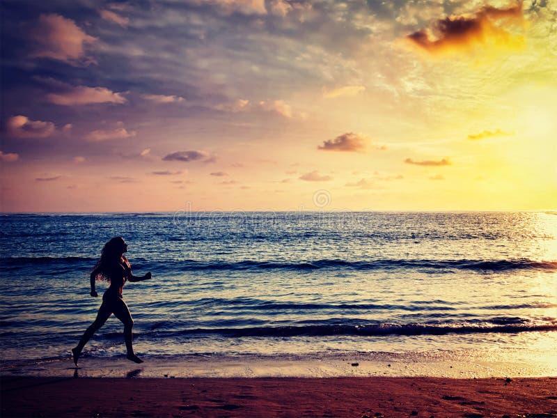 Härlig idrotts- kvinnaspring längs havet på stranden royaltyfri bild