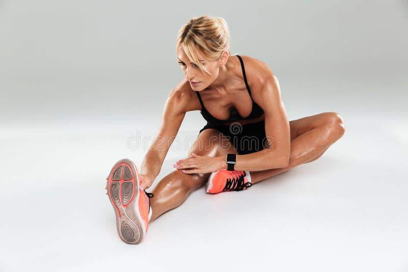 Härlig idrottsman nenkvinna som gör sträcka övningar arkivfoto