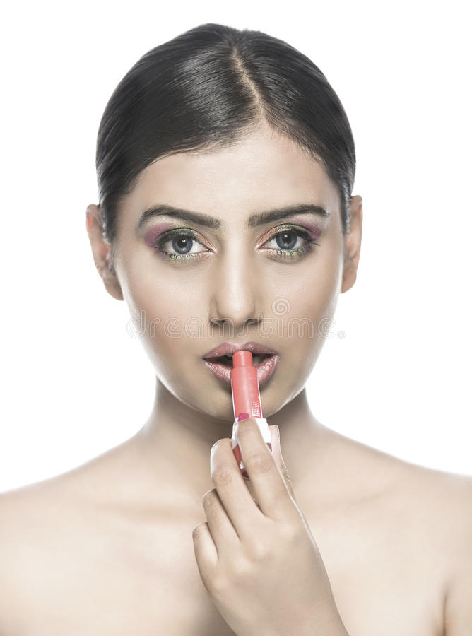 Härlig indisk flicka som applicerar läppstift eller lipcolor arkivfoto