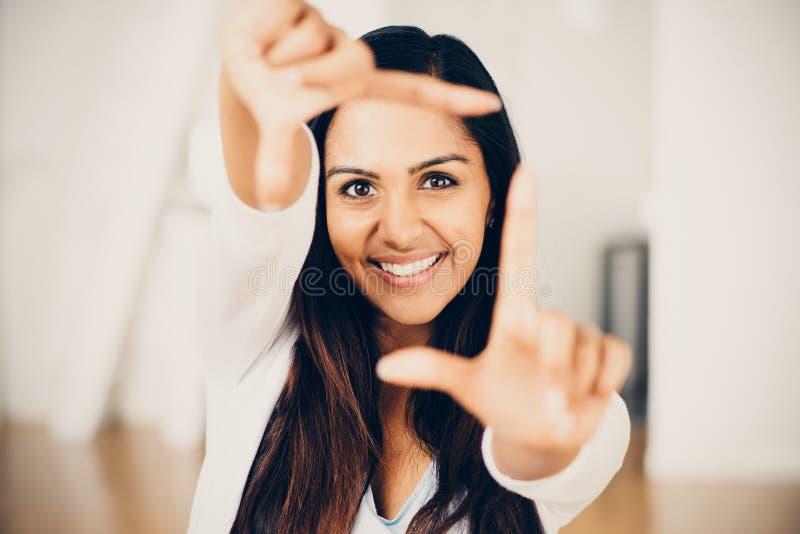 Härlig indisk kvinna som inramar lyckligt le för fotografi royaltyfria bilder